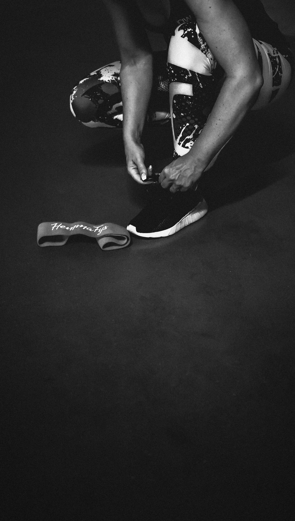 grayscale photo of person wearing sneakers