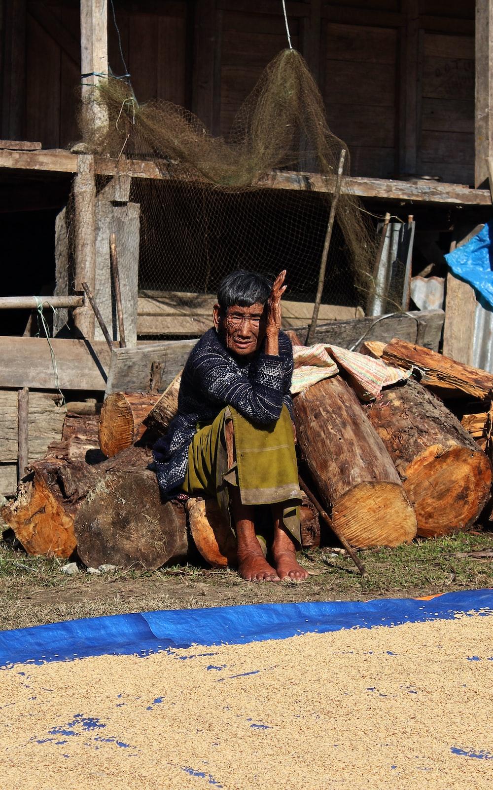 man in black and gray plaid dress shirt sitting on brown wood log