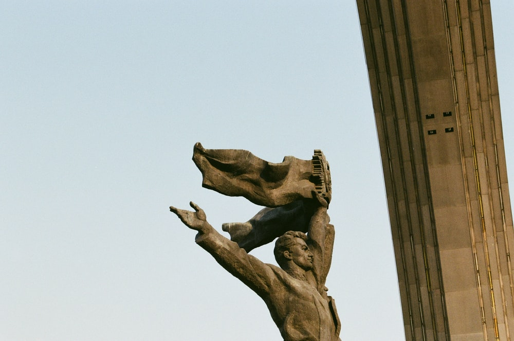 brown concrete statue under blue sky during daytime