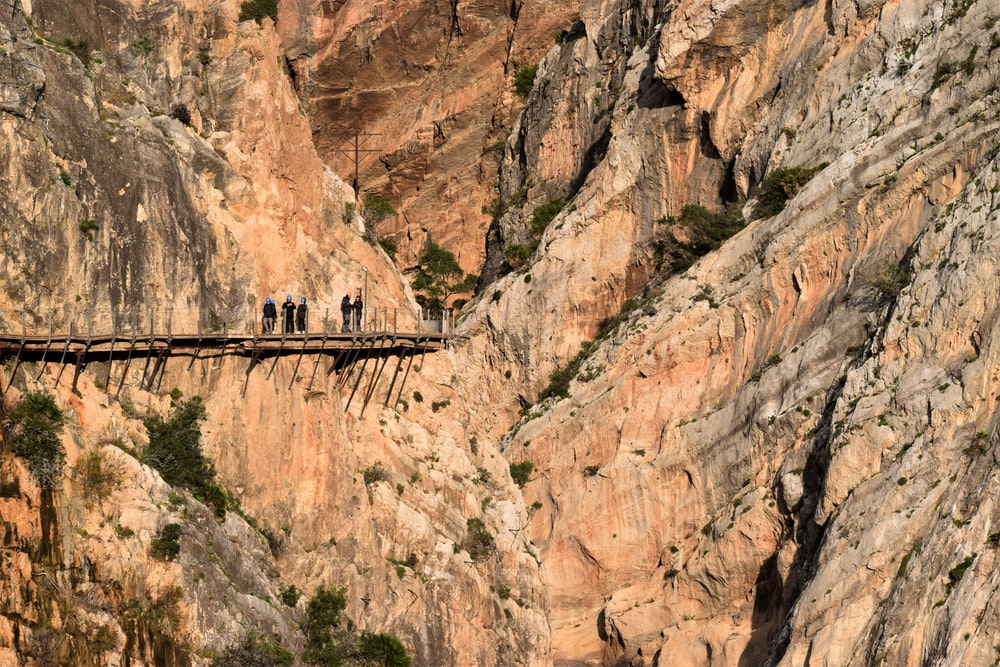 brown wooden bridge on brown rocky mountain during daytime