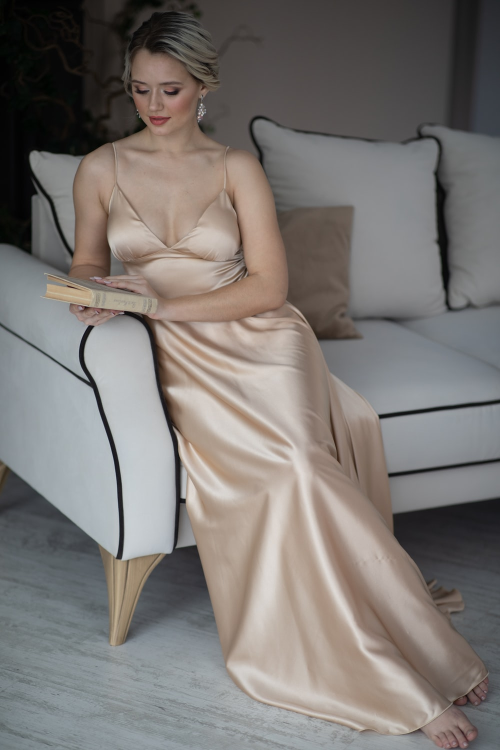 woman in white dress sitting on white couch