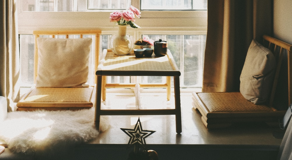 white and brown wooden table with white and pink flower on top