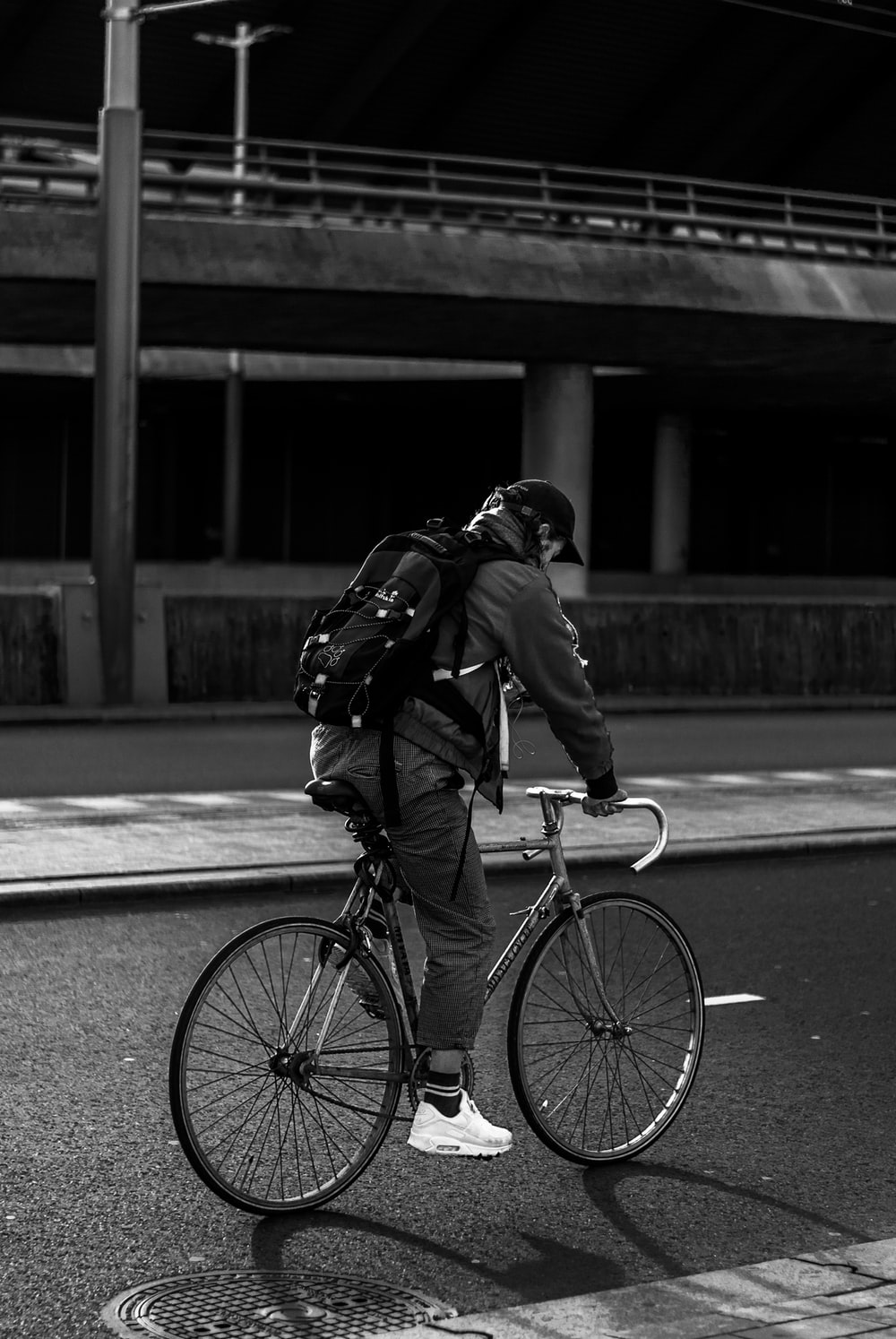 man in black jacket and pants riding bicycle on road during daytime