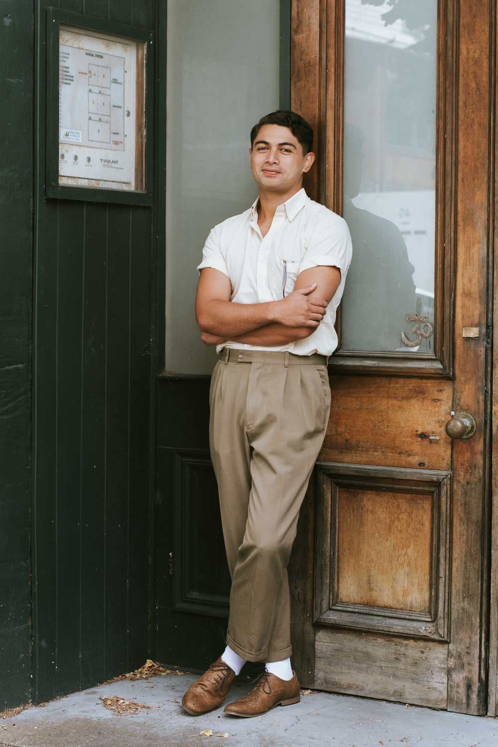 man in white button up shirt and brown pants standing beside brown wooden door