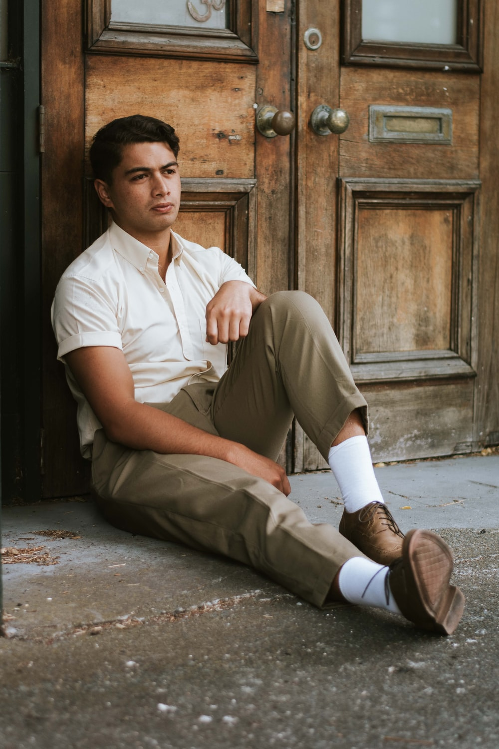 man in white button up shirt and brown pants sitting on concrete floor