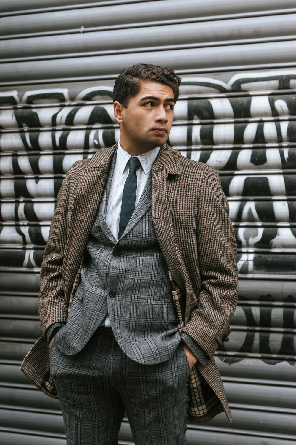 man in brown suit jacket standing near gray wall