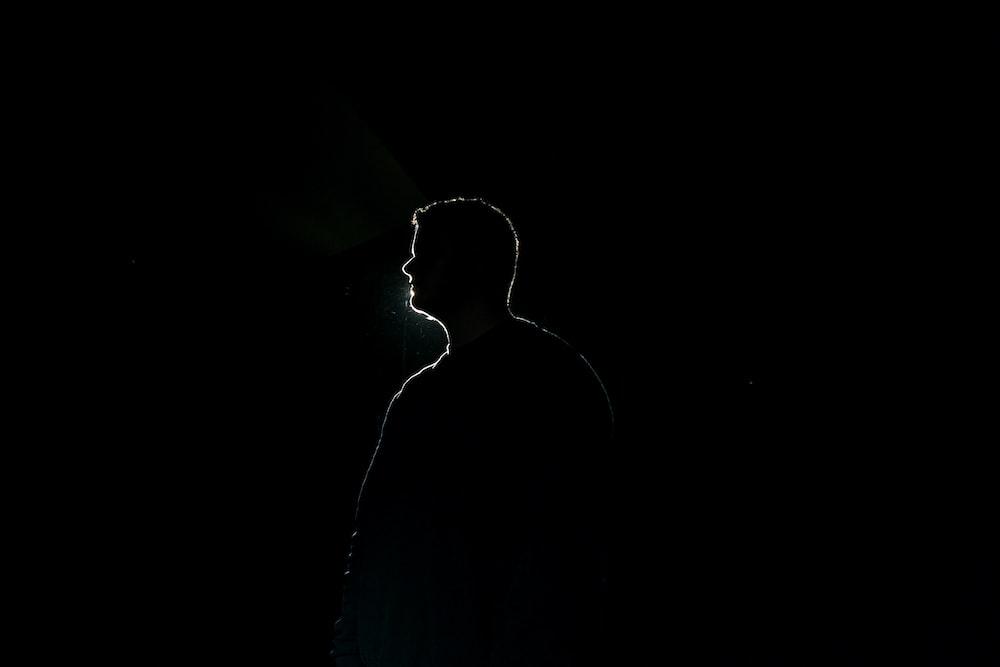 silhouette of man standing in dark room