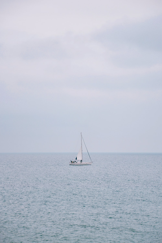 white sailboat on sea under white sky during daytime
