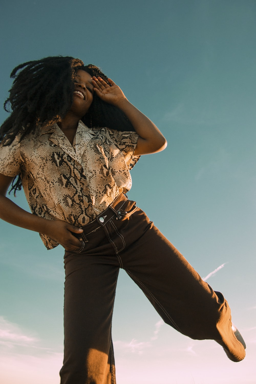 woman in white and black floral shirt and brown pants
