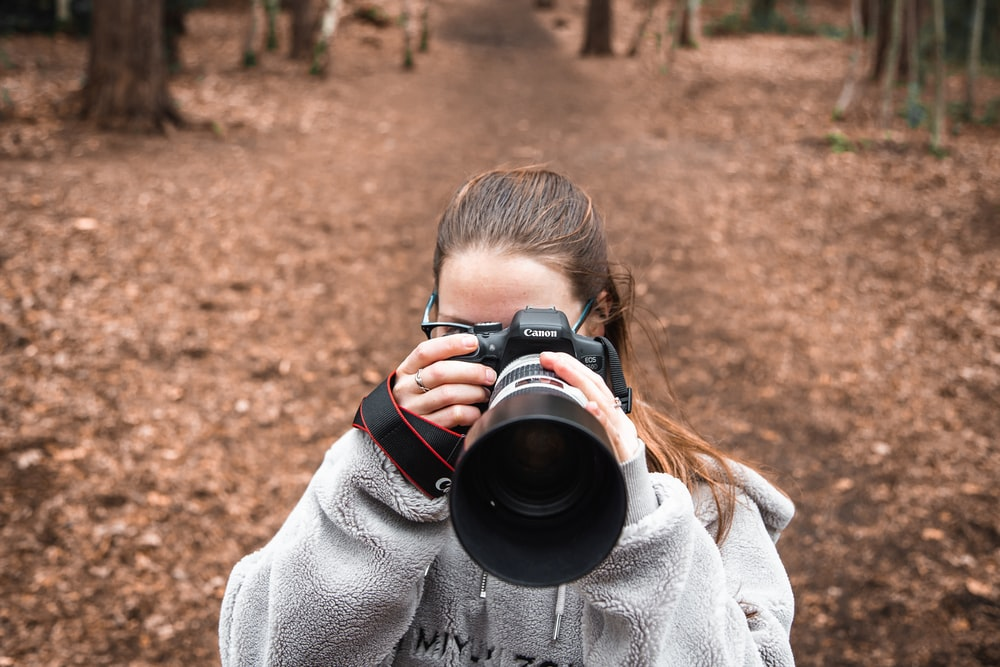 woman in gray sweater holding black dslr camera