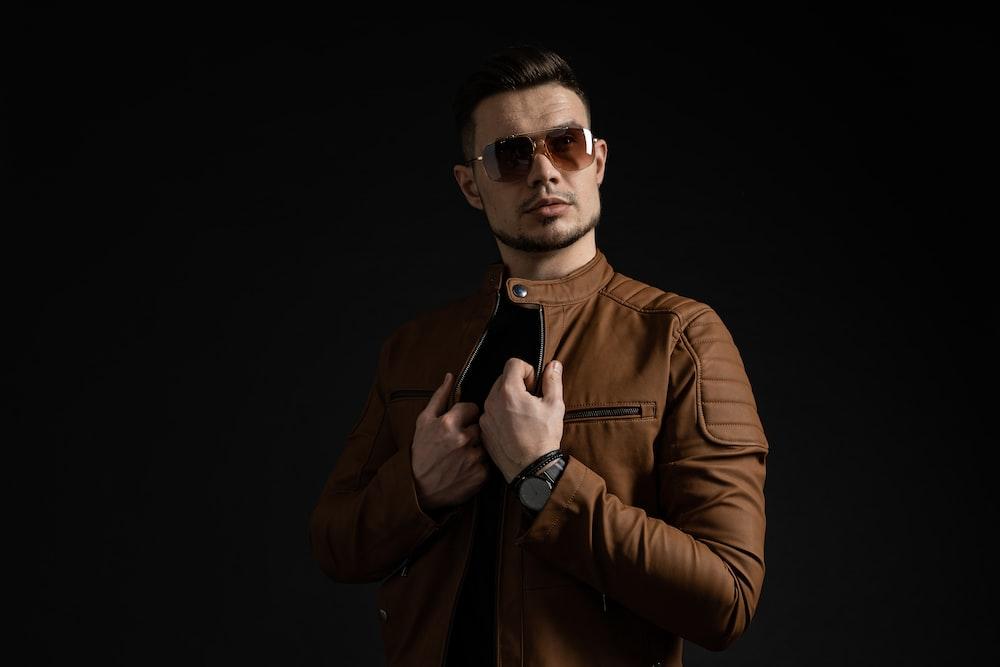 man in brown leather jacket wearing black sunglasses