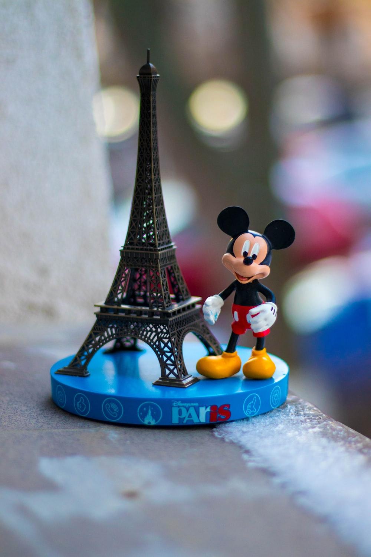 mickey mouse figurine beside eiffel tower miniature