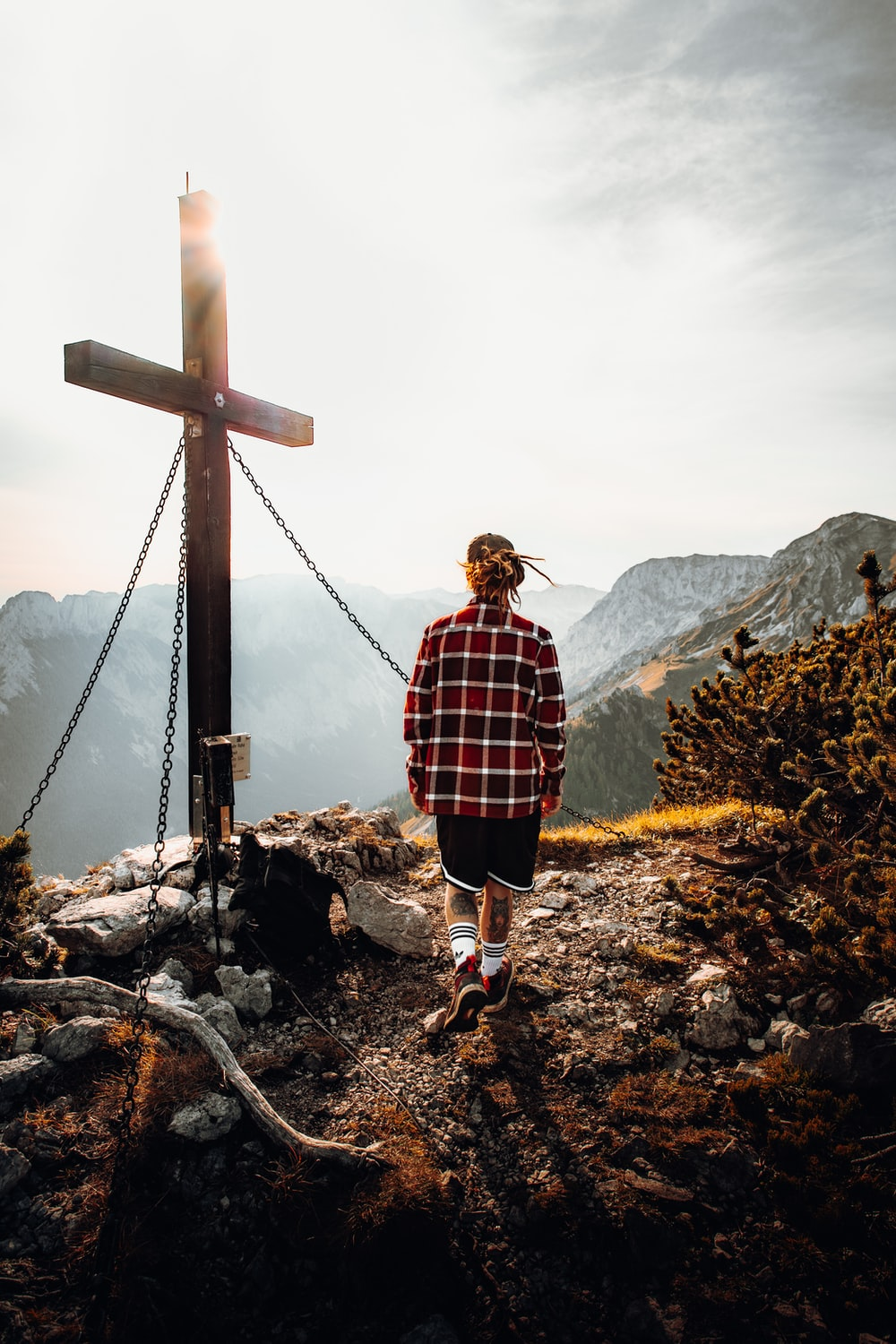 woman in red and black plaid dress shirt standing on brown wooden cross during daytime