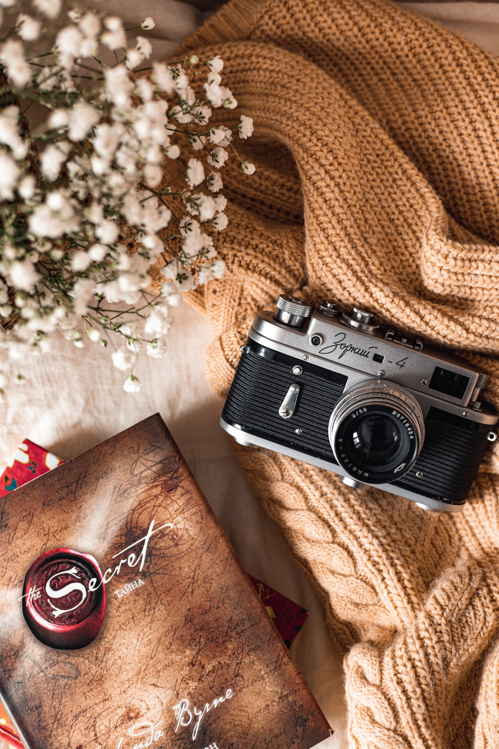 black and silver camera on brown textile