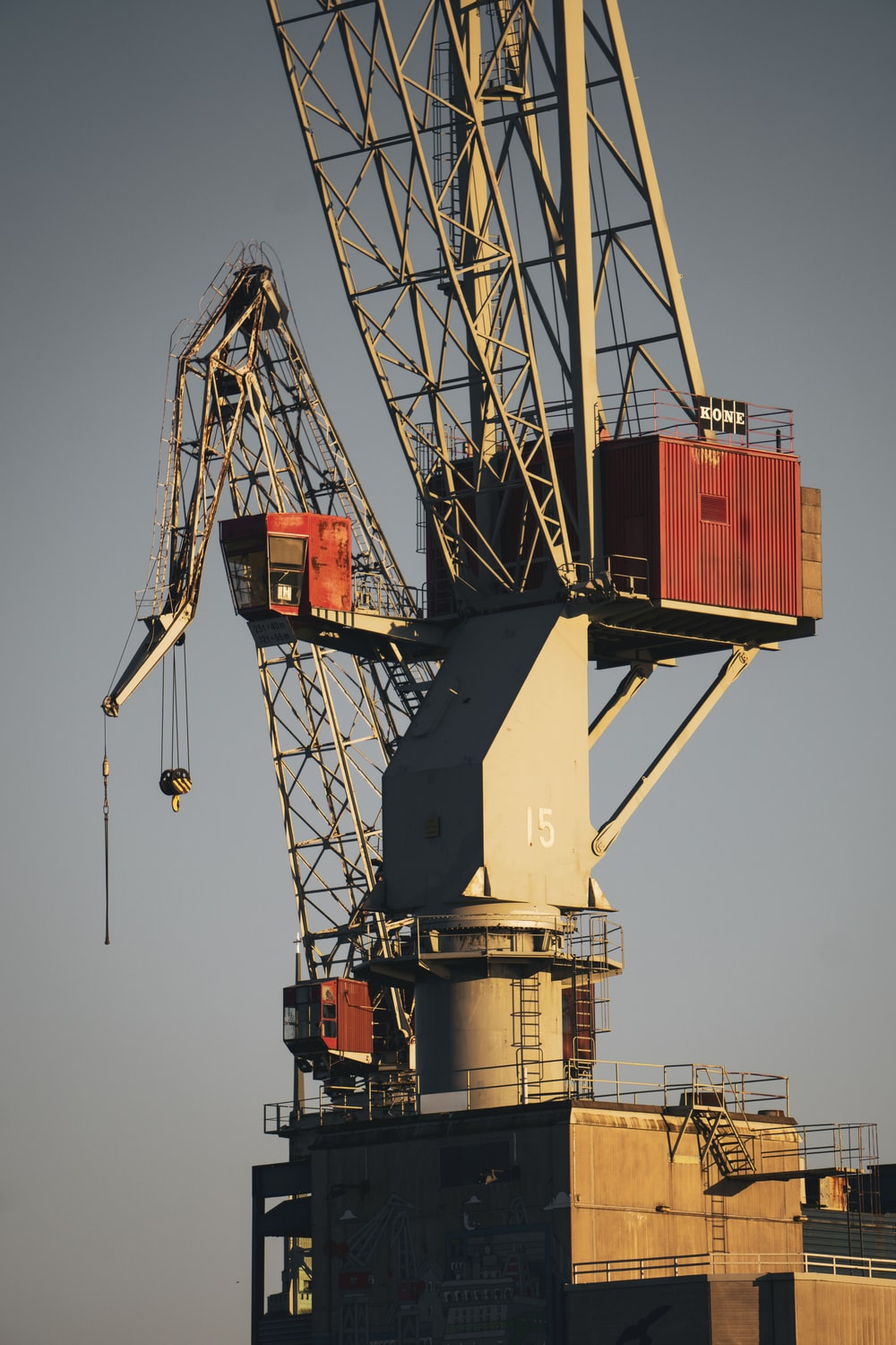 white and red crane under blue sky during daytime