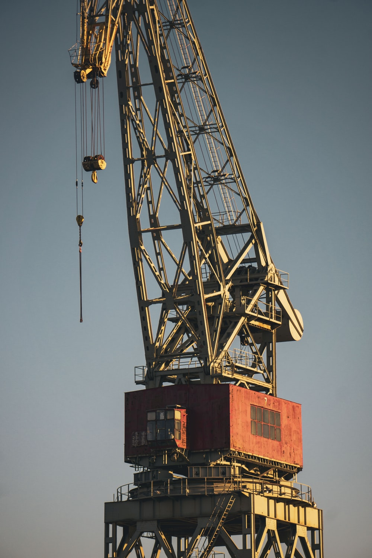 red and black crane under blue sky during daytime