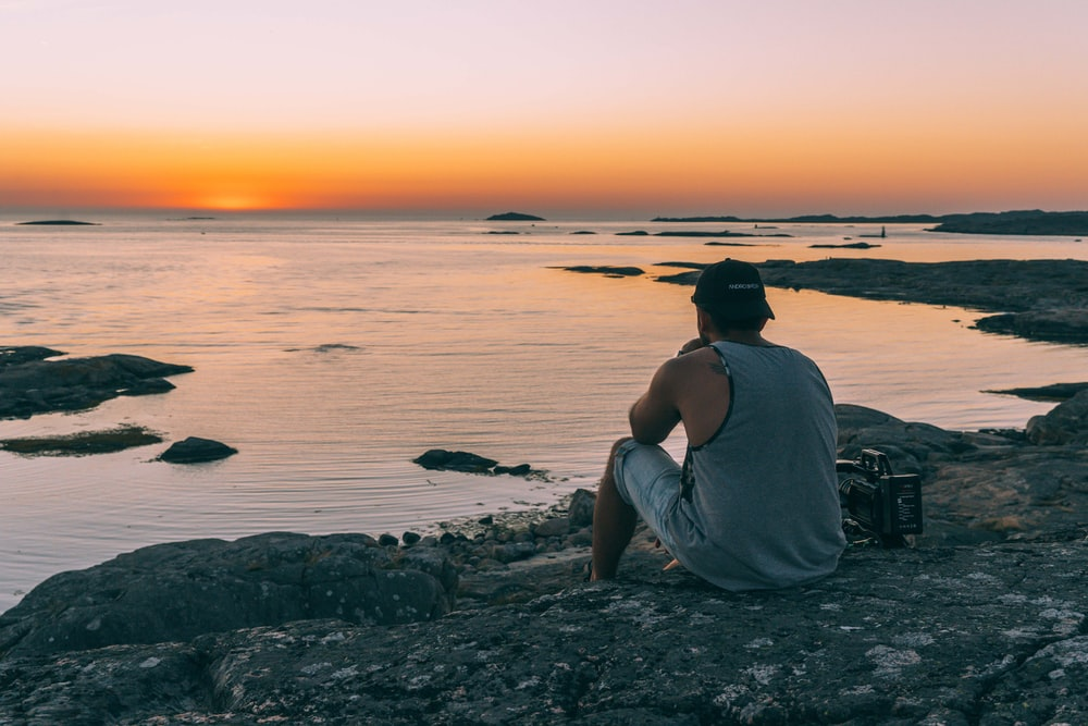 man in gray tank top sitting on rocky shore during sunset