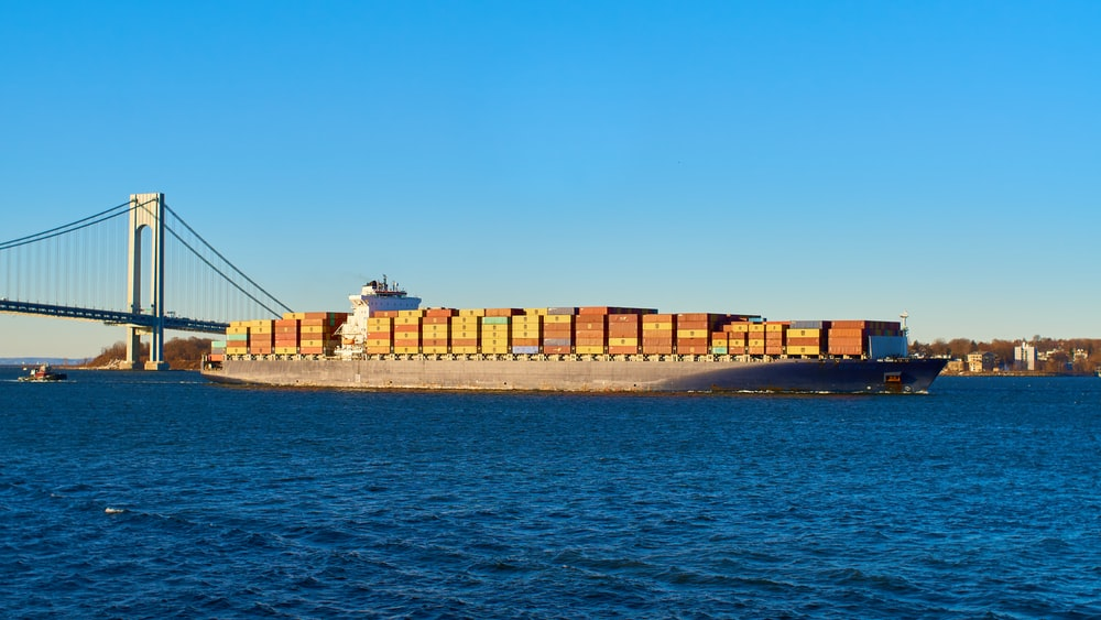 brown cargo ship on sea under blue sky during daytime