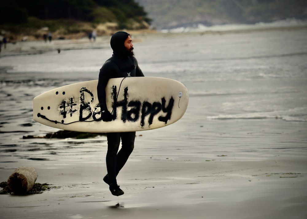 man in black hoodie carrying white surfboard walking on beach during daytime