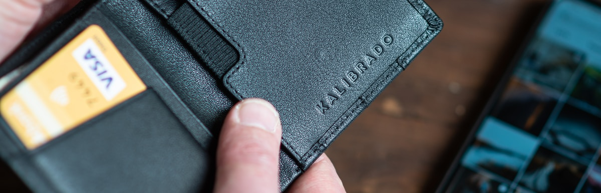 black leather bifold wallet on persons hand