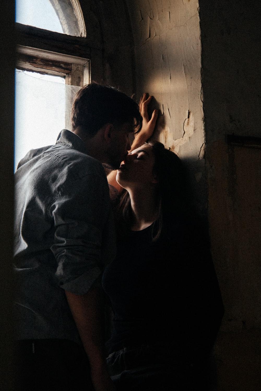 man in gray shirt hugging woman in black tank top
