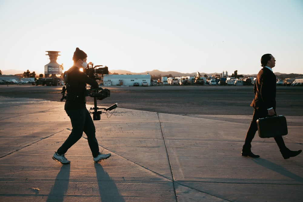 man in black jacket and pants standing on gray concrete floor during sunset