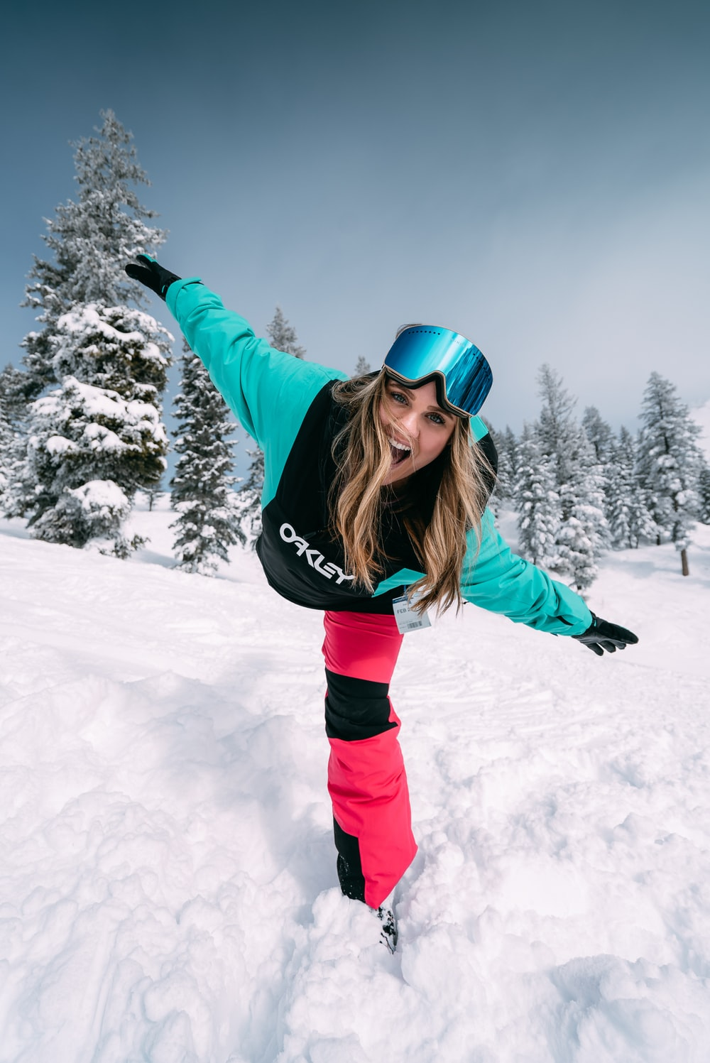 woman in green jacket and black pants on snow covered ground