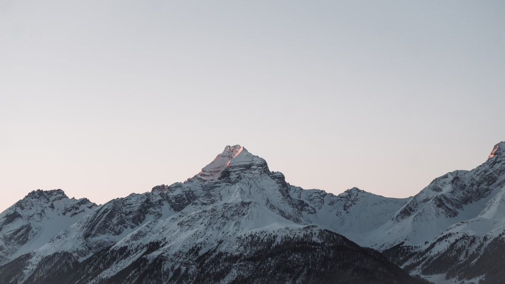 snow covered mountain under white sky during daytime