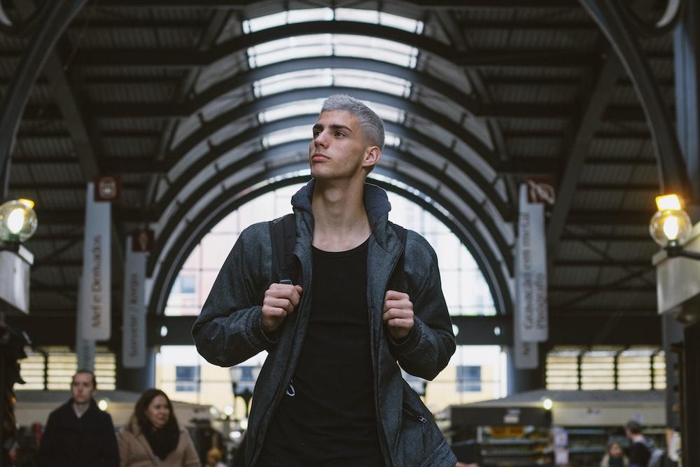 man in black jacket standing near people