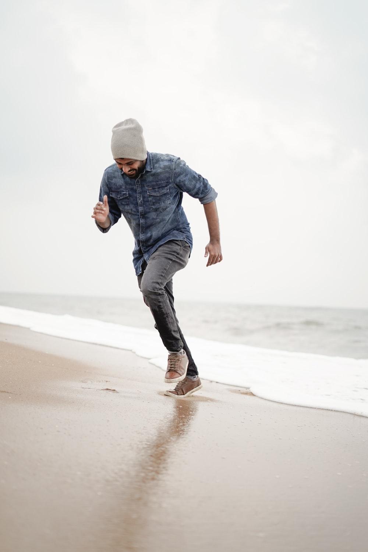man in blue denim jacket and black pants walking on beach during daytime