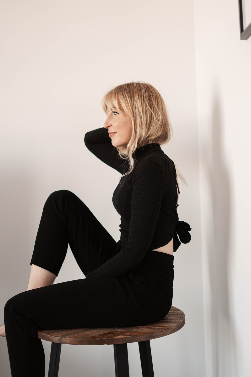woman in black long sleeve shirt and black pants sitting on white wall