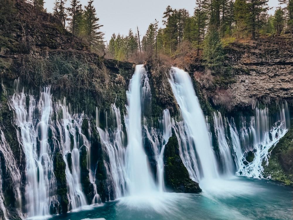 waterfalls on brown rocky mountain during daytime