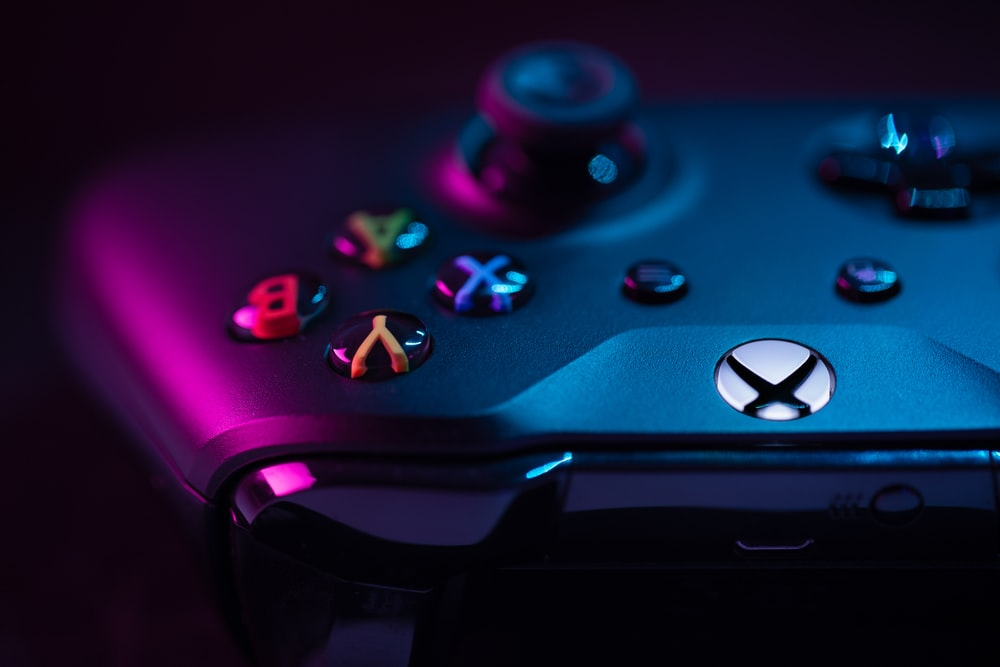 blue xbox game controller with blue and white lights