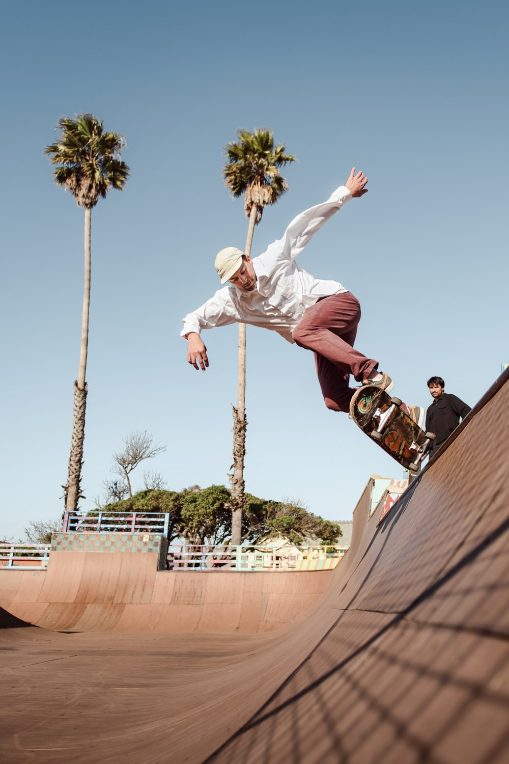 man in white shirt and brown pants jumping on brown concrete wall during daytime