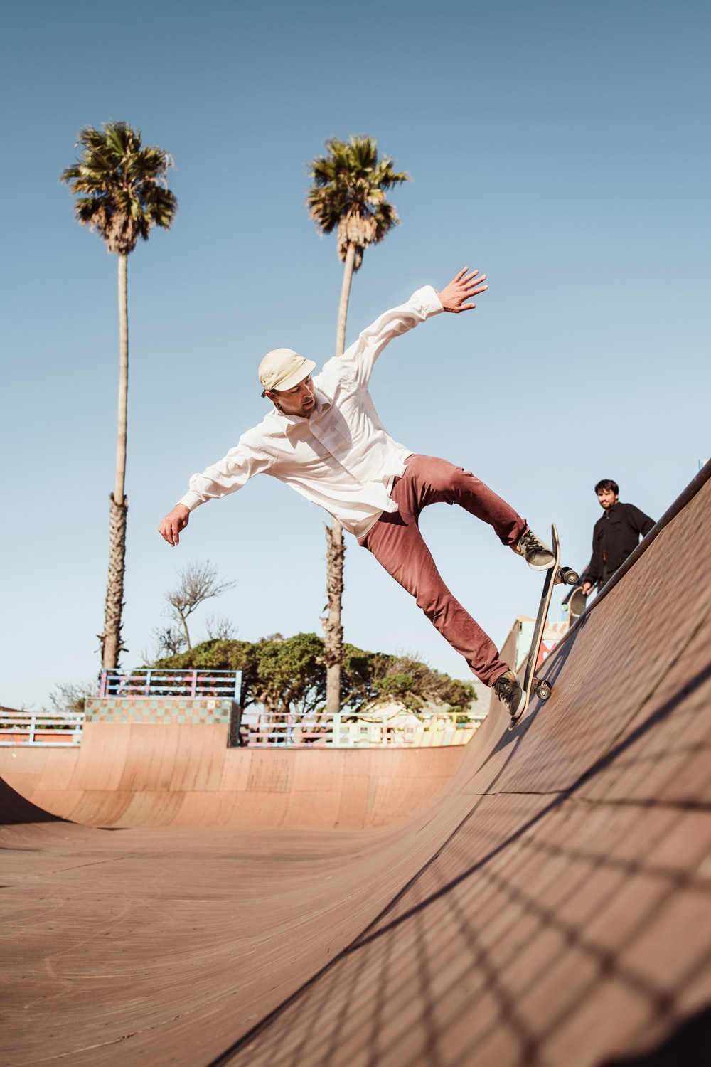 man in white shirt and brown pants riding skateboard during daytime