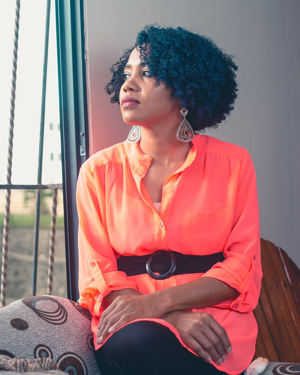 woman in orange button up shirt sitting on brown wooden chair