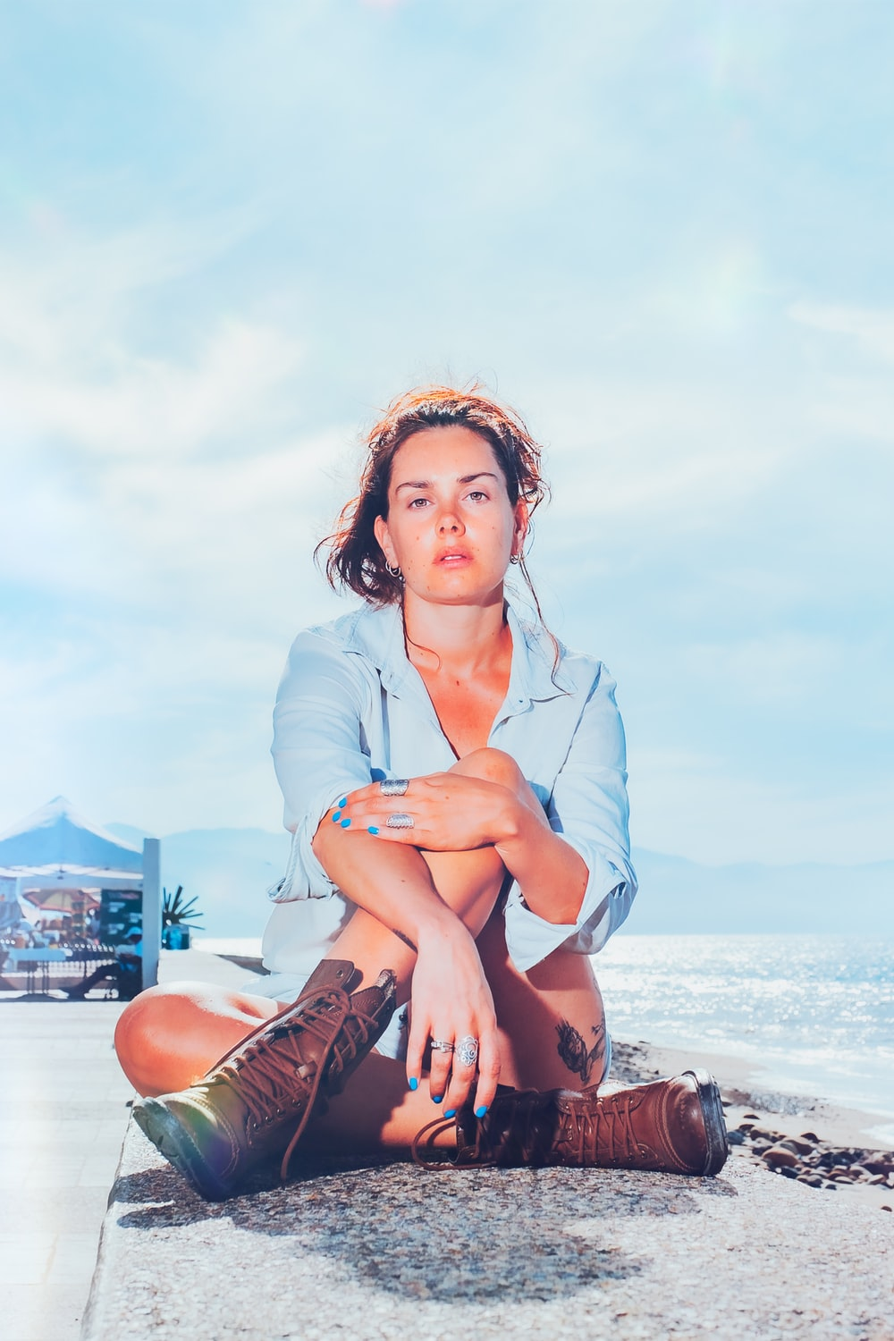 woman in blue button up shirt and brown leather boots sitting on beach during daytime