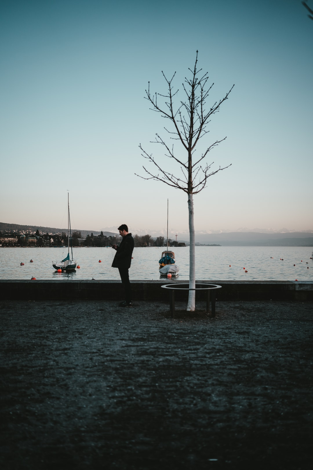 couple standing on dock near body of water during daytime