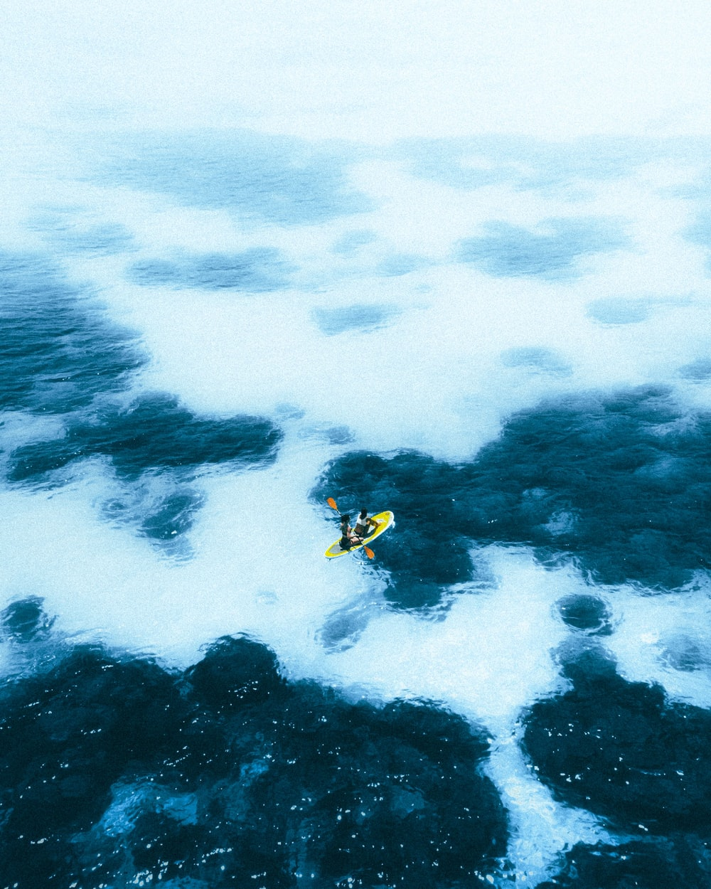 person in yellow and black wetsuit surfing on blue ocean water during daytime