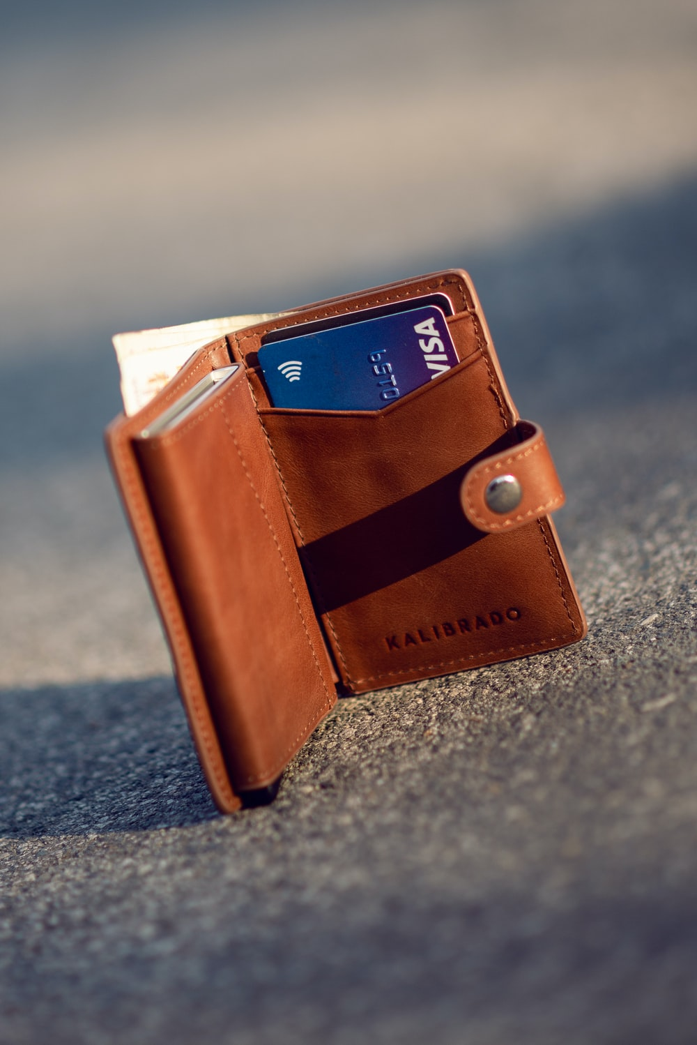 brown leather bifold wallet on gray concrete floor