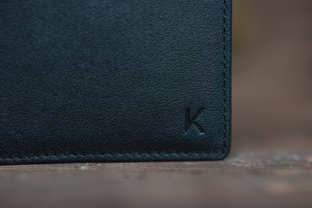 black leather bifold wallet on white table