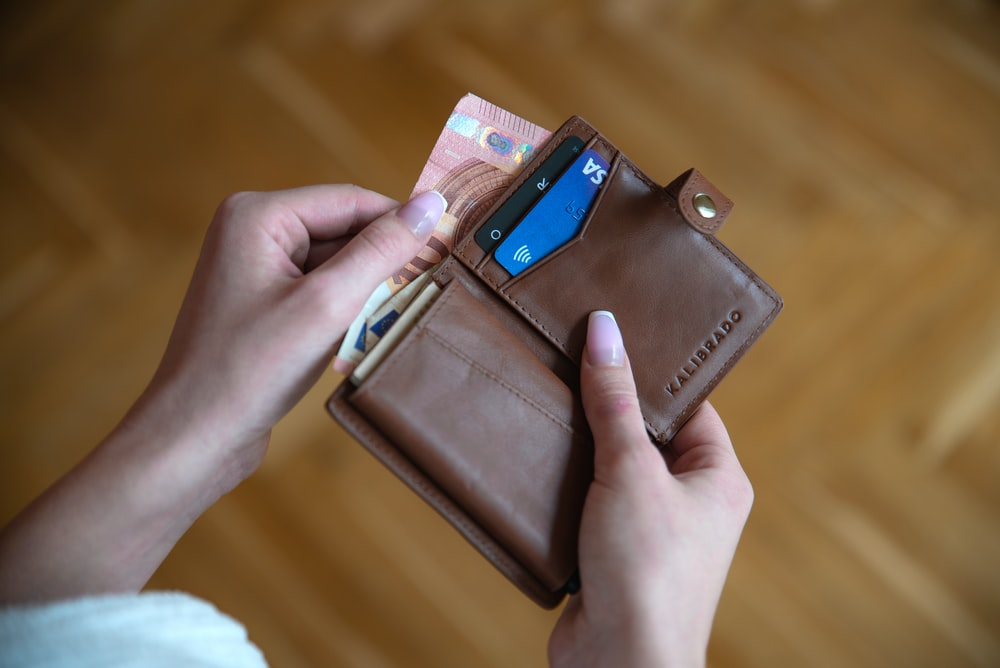 person holding brown leather card wallet