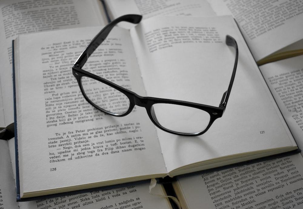 black framed eyeglasses on white printer paper