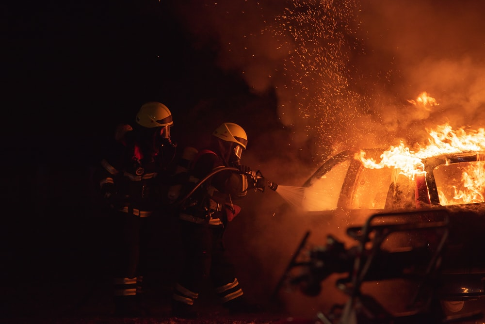 2 men in black helmet standing near fire