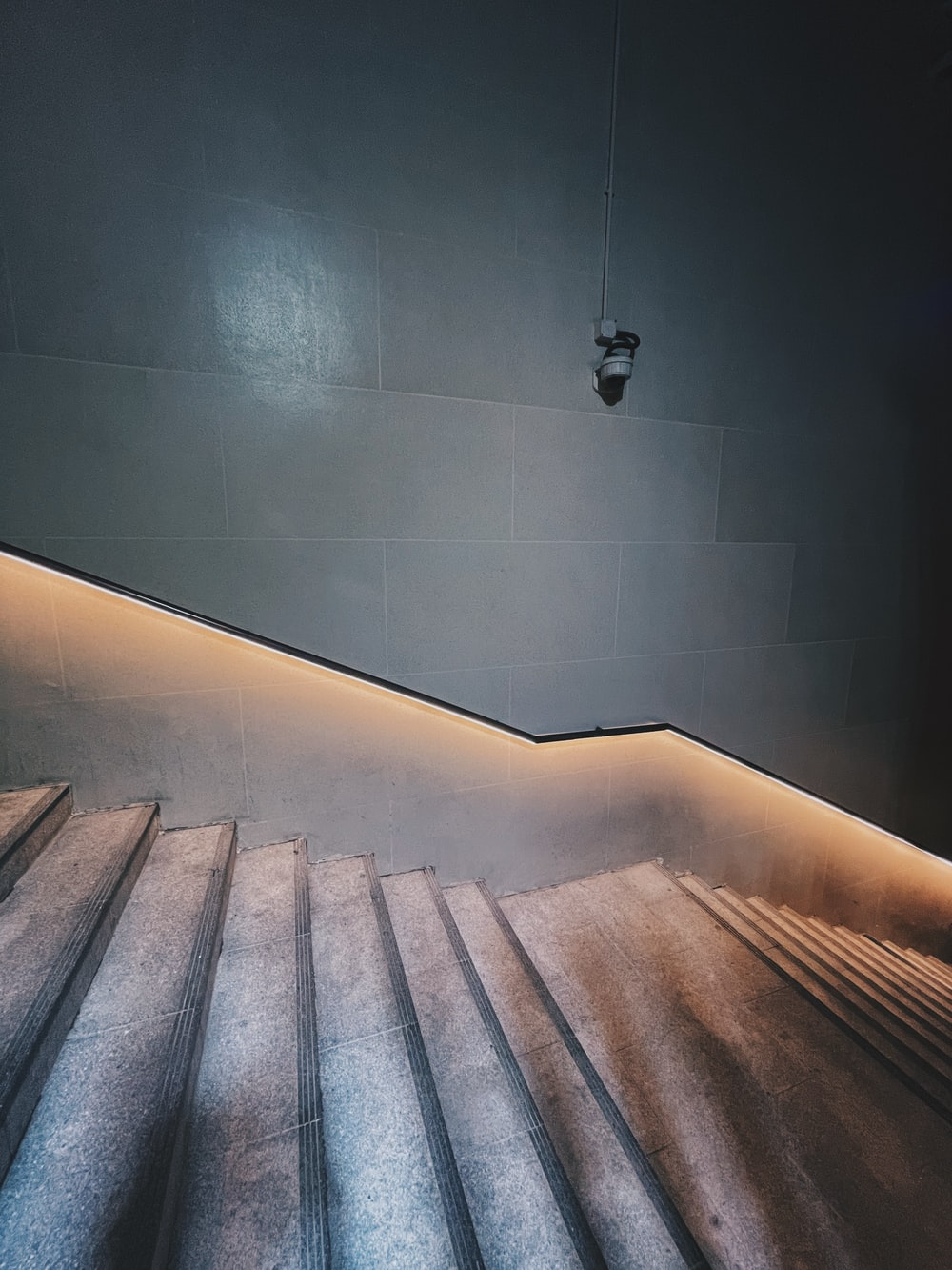brown wooden staircase on black tiled wall