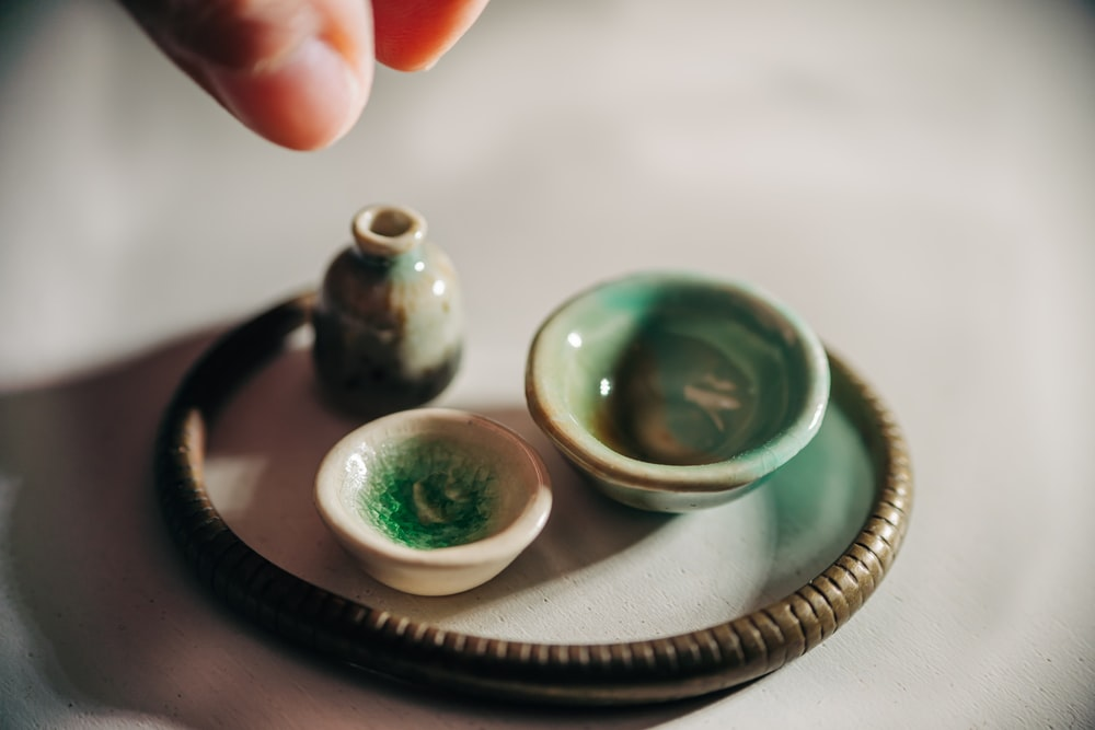person holding 2 green and white ceramic bowls