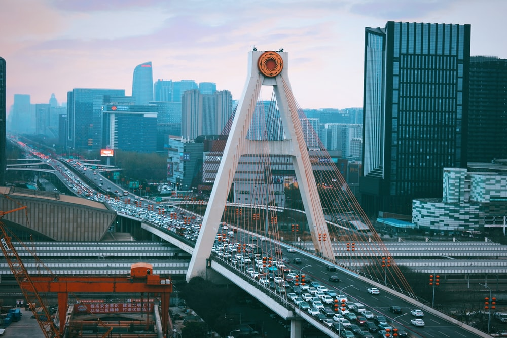 white bridge over city buildings during daytime