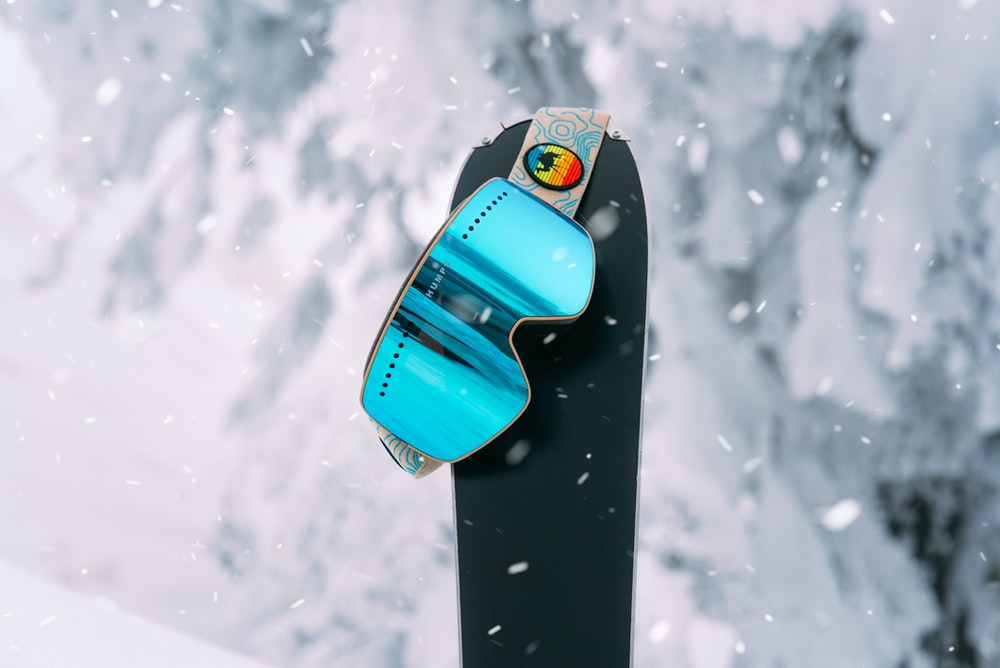 blue and black surfboard on snow covered ground