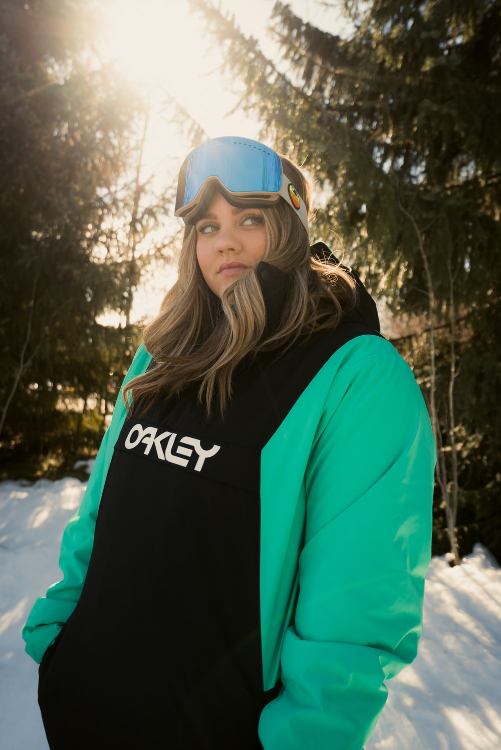 woman in blue and black hoodie wearing white and blue fitted cap