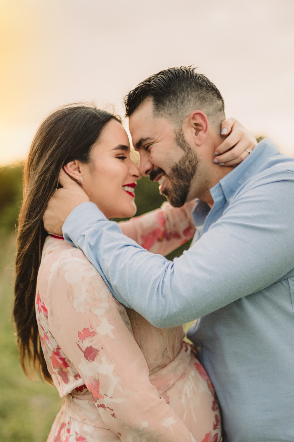 man in blue dress shirt kissing woman in white floral dress